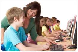 Female teacher assisting students in a computer classroom